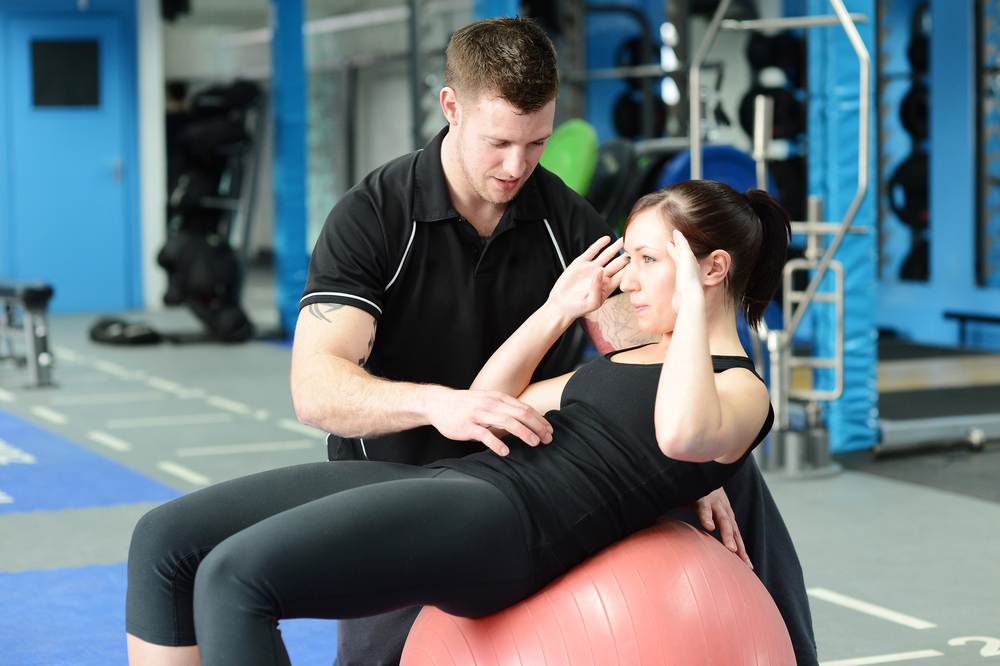 Male personal trainer with female client on swiss ball